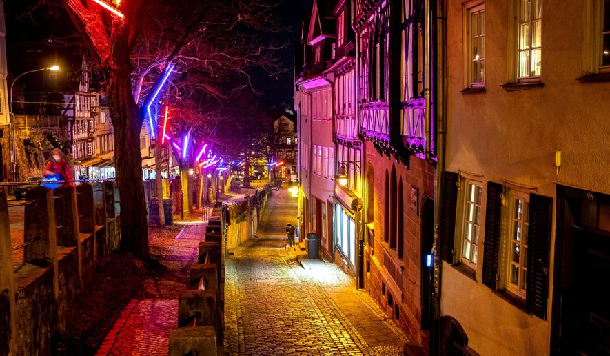 Christmas lights hang in the trees as the streets are almost empty in the old town of Marburg, Germany, Monday, Nov. 30, 2020. (AP Photo/Michael Probst)