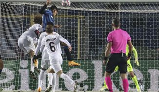 Cristian Romero of Atlanta, top, takes a header at Midtjylland goal in an unsuccessful attempt, during their Group D, Champions League soccer match between Atalanta and FC Midtjylland, at the Geweiss stadium in Bergamo, Italy, Tuesday, Dec. 1, 2020. (Stefano Nicoli/LaPresse via AP)