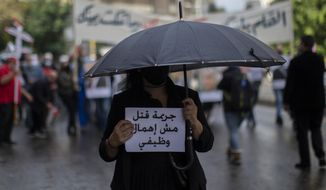"""An anti-government protester holds an Arabic sign that reads: """"It is a criminal murder, not negligence,"""" during a protest in Beirut's Ashrafieh district, Lebanon, Thursday, Nov. 26, 2020. Dozens of protesters rallied Thursday outside the house of Judge Fadi Sawwan, the lead judicial investigator into the catastrophic blast at Beirut's port in August the blast that killed nearly 200 people, wounded more than 6,000 and caused billions of dollars in damage. (AP Photo/Hassan Ammar)"""