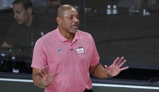 """In this Sept. 15, 2020, file photo, Los Angeles Clippers head coach Doc Rivers questions a call during the first half of an NBA conference semifinal playoff basketball game against the Denver Nuggets in Lake Buena Vista, Fla. Rivers is now head coach of the Philadelphia 76ers. The first preseason camps of the coronavirus era are formally open, with teams limited for now to individual sessions with one coach and one player at one basket, all of this starting to happen as the pandemic continues raging and more and more Americans are testing positive.  """"I'm very concerned if we can pull this off,"""" Philadelphia coach Doc Rivers said.  (AP Photo/Mark J. Terrill, File)  **FILE**"""