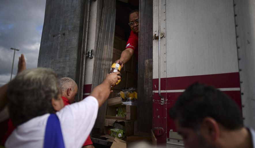 In this Wednesday, Jan. 8, 2020, photo, residents receive aid supplies after suffering the previous day's magnitude 6.4 quake in Yauco, Puerto Rico. A key U.N. aid agency says needs for humanitarian assistance have ballooned this year because of COVID-19, projecting that a staggering 235 million people — who together would make up the world's fifth-most populous country — are likely to require such help next year for troubles like the pandemic as well as war, forced migration and the impact of global warming. (AP Photo/Carlos Giusti) **FILE**