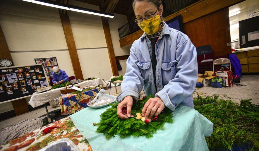 Members of the All Souls Unitarian Universalist Church, in Brattleboro, Vt., make wreaths on Monday, Nov. 30, 2020, for the annual Holiday Bazaar. (Kristopher Radder/The Brattleboro Reformer via AP)
