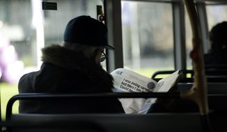 A man reads a newspaper with an article about COVID-19 as he sits on a bus during England's second coronavirus lockdown in London, Tuesday, Dec. 1, 2020. England's second coronavirus lockdown is due to end tomorrow to be replaced by a three-tier system. (AP Photo/Matt Dunham)