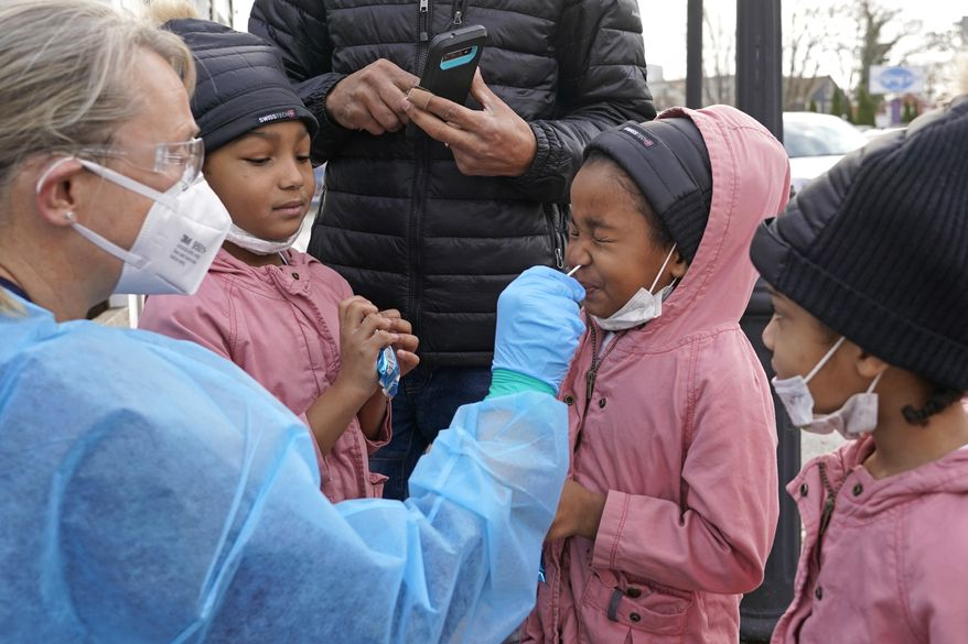 Vivian de Pina, 5, receives a COVID-19 test as her sisters Carla, 6, left, and Kataleya, 4, watch, Tuesday, Dec. 1, 2020, in Chelsea, Mass. (AP Photo/Elise Amendola)