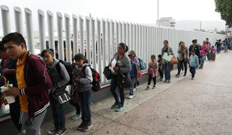 This July 26, 2018, photo shows people lining up to cross into the United States to begin the process of applying for asylum near the San Ysidro port of entry in Tijuana, Mexico. A court-appointed committee has yet to find the parents of 628 children separated at the border early in the Trump administration. (AP Photo/Gregory Bull) **FILE**