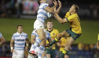 Argentina's Emiliano Boffelli, left, battles for the ball with Australia's Reece Hodge in the air during their Tri-Nations rugby union match in Newcastle, Australia, Saturday, Nov. 21, 2020. (AP Photo/Rick Rycroft)