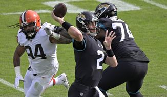 Jacksonville Jaguars quarterback Mike Glennon (2) throws a pass as he is rushed by Cleveland Browns defensive end Adrian Clayborn, left, during the first half of an NFL football game, Sunday, Nov. 29, 2020, in Jacksonville, Fla. (AP Photo/Phelan M. Ebenhack)