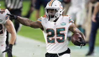 Miami Dolphins cornerback Xavien Howard (25) points and runs with the ball after intercepting a pass from Los Angeles Chargers quarterback Justin Herbert (not shown) during an NFL football game, Sunday, Nov. 15, 2020, in Miami Gardens, Fla. Howard leads the NFL this season with seven interceptions, and his shutdown skills have helped the Dolphins flummox foes with a blitz-happy scheme. (AP Photo/Doug Murray)