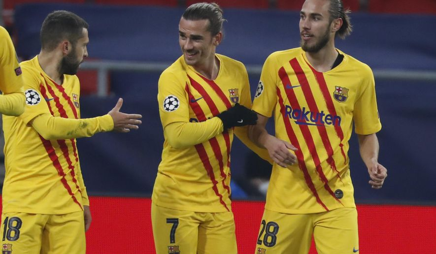 Barcelona's Antoine Griezmann, center, celebrates after scoring his side's opening goal during the Champions League group G soccer match between Ferencvaros and Barcelona at the Ferenc Puskas stadium in Budapest, Hungary, Wednesday, Dec. 2, 2020. (AP Photo/Laszlo Balogh)