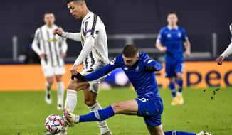 Cristiano Ronaldo of Juventu, left, escapes a Dynamo Kyiv challenge during a Champions League, group G soccer match between Juventus and Dinamo Kyiv at the Allianz Stadium in Turin, Italy, Wednesday, Dec. 2, 2020. (Marco Alpozzi/LaPresse via AP)