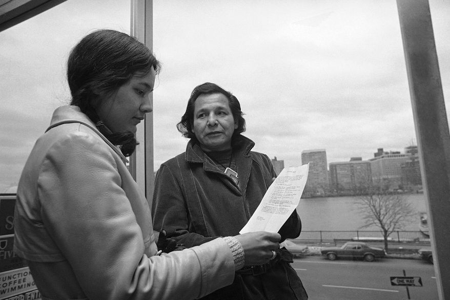 FILE - in this Nov. 4, 1971 file photo, Eddie Benton, a holy man of the Chippewa Indian Tribe, shows a prayer he wrote to Linda Jeffers, of Vineyard Haven, Martha's Vineyard, Mass., a member of the Wampanoag Tribe in Cambridge, Mass. Eddie Benton-Banai, one of the founders of the American Indian Movement that was formed partly in response to alleged police brutality against Indigenous people, has died. He was 89. A family friend says Benton-Banai died Monday, Nov. 30, 2020 at a care center in Hayward, Wis., where he had been staying for months. (AP Photo/J. Walter Green, File)
