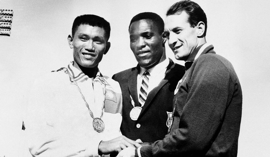 In this Sept. 7, 1960, file photo, Rafer Johnson of Kingsburg, Calif., is flanked by runners-up, Chuan-Kwang Yang, left, of Taiwan, and Vasily Kuznetsov of Russia, as they join in three-way handshake after receiving medals for the decathlon event of the Olympics in Rome, Italy. Rafer Johnson, who won the decathlon at the 1960 Rome Olympics and helped subdue Robert F. Kennedy's assassin in 1968, died Wednesday, Dec. 2, 2020. He was 86. He died at his home in the Sherman Oaks section of Los Angeles, according to family friend Michael Roth. (AP Photo) **FILE**