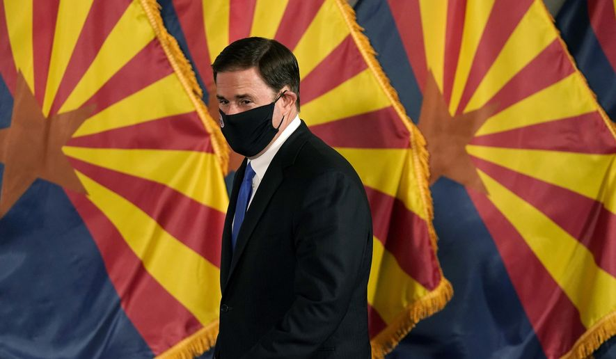 Arizona Republican Gov. Doug Ducey arrives for a news conference to talk about the latest Arizona COVID-19 information Wednesday, Dec. 2, 2020, in Phoenix. (AP Photo/Ross D. Franklin, Pool)