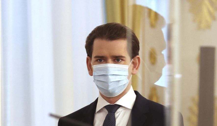 Austrian Chancellor Sebastian Kurz wears a face mask as he arrives behind plexiglass shields for a press conference at the federal chancellery in Vienna, Austria, Wednesday, Dec. 2, 2020. The Austrian government has moved to restrict freedom of movement for people, in an effort to slow the onset of the COVID-19 coronavirus. (AP Photo/Ronald Zak)