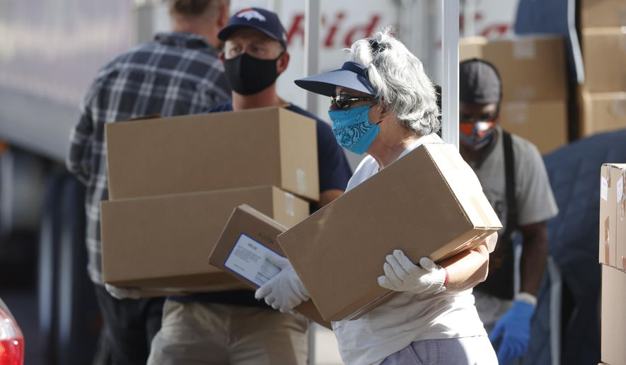 In this June 26, 2020, file photo, volunteers Juanita MacKenzie, front, and Dave Stutman carry boxes of food to a waiting car at a large mobile pantry set up by the Food Bank of the Rockies in the parking lot of Empower Field at Mile High in west Denver. In an effort to keep Colorado residents fed and employed this winter, Colorado's Legislature is concluding a special session Wednesday, Dec. 2, 2020, by passing bills offering assistance to restaurants and food pantries struggling to keep their doors open during the coronavirus pandemic. (AP Photo/David Zalubowski, File)