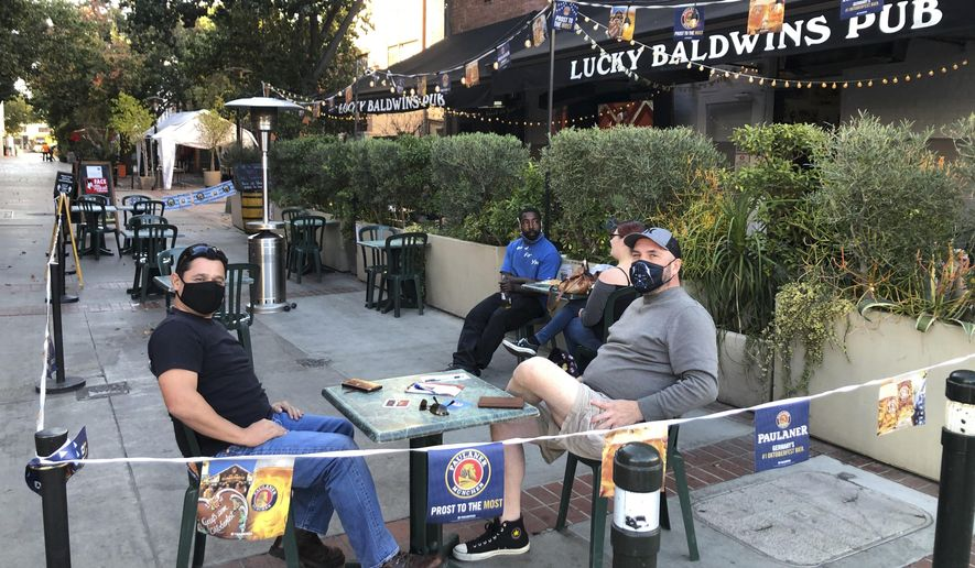 Anthony Angulo, left, and Jeff Koloski sit on the patio of Lucky Baldwin's pub on Monday, Nov. 30, 2020 in Pasadena, Calif. It was a rare sight after restaurants in Los Angeles County were ordered to halt serving food to diners to stop the spread of coronavirus: tables and chairs were set up outdoors in Pasadena. The city in the Los Angeles suburbs has become an island in the center of the nation's most populous county, where a surge of COVID-19 cases last week led to a three-week end to outdoor dining and California's first stay-home order since the pandemic began to spread across the state in March. (AP Photo/Christopher Weber)