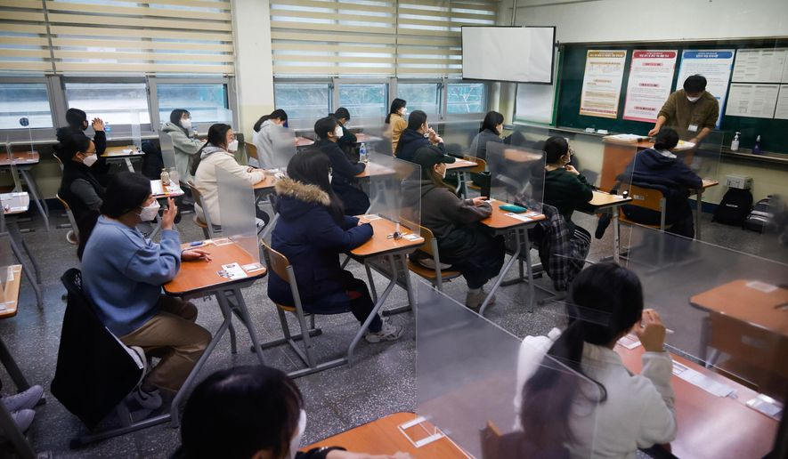 Students wearing face masks wait for the start of the annual college entrance examination amid the coronavirus pandemic at an exam hall in Seoul, South Korea, Thursday, Dec. 3, 2020. South Korean officials are urging people to remain at home if possible and cancel gatherings as about half a million students prepare for a crucial national college exam. (Kim Hong-Ji/Pool Photo via AP)