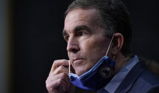 Virginia Gov. Ralph Northam removes his mask to answer a question during a COVID-19 briefing at the Capitol in Richmond, Va, Wednesday Nov 18, 2020. (AP Photo/Steve Helber)