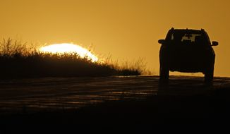 FILE - In this Oct. 1, 2020, file photo, a motorist drives into the sunrise in Kansas City, Mo. At a board meeting Tuesday, Dec. 1, 2020, the Alliance for Automotive Innovation, a big industry trade association, recognized that change is coming. Alliance CEO John Bozzella said automakers are committed to working with the Biden administration, which will renew the fight against climate change and likely will undo pollution and gas mileage rollbacks made by President Donald Trump. (AP Photo/Charlie Riedel)