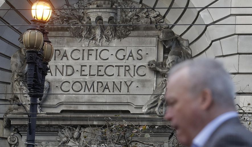 FILE - In this Dec. 16, 2019, file photo, is a man walking past a Pacific Gas and Electric sign on a PG&E building in San Francisco. PG&E's household customers will be hit with an average rate increase of 8% to help the once-bankrupt utility pay for improvements designed to reduce the risks that its outdated equipment will ignite deadly wildfires in its Northern California service territory. The higher prices, effective March 1, are expected to boost the bills of PG&E's residential customers by an average of $13.44 to per month.  (AP Photo/Jeff Chiu, File)