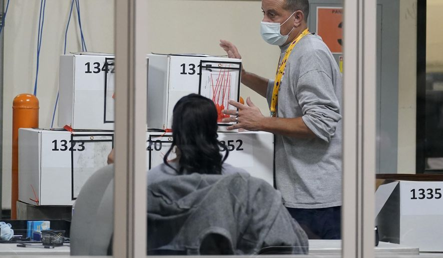 In this Nov. 5, 2020 file photo, a county election worker moves boxes of mail-in ballots at a tabulating area at the Clark County Election Department in Las Vegas. (AP Photo/John Locher, File)