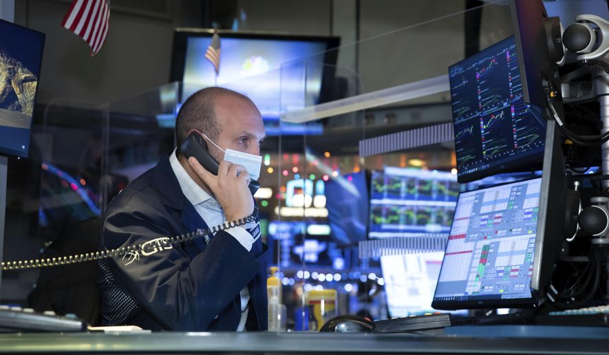 In this photo provided by the New York Stock Exchange, specialist James Denaro works at his post on the trading floor, Thursday Dec. 3, 2020. U.S. stocks are inching further into record heights Thursday, as Wall Street continues to coast following its rocket ride last month powered by hopes for coming COVID-19 vaccines. (Nicole Pereira/New York Stock Exchange via AP)