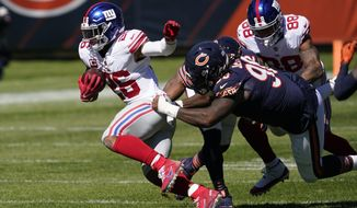 FILE - In this Sept. 20, 2020, file photo, New York Giants running back Saquon Barkley (26) tries to break free from Chicago Bears defensive tackle John Jenkins (90) during the first half of an NFL football game in Chicago. Barkley has had surgery to repair a torn ACL in his right knee. Coach Joe Judge confirmed the surgery on Saturday, Oct. 31, 2020, without giving specifics. (AP Photo/Charles Rex Arbogast, File)