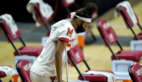 Maryland forward Angel Reese walks with crutches while on the bench during the second half of an NCAA college basketball game against Towson, Thursday, Dec. 3, 2020, in College Park, Md. Maryland won 112-78. (AP Photo/Julio Cortez)
