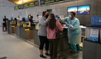 In this Nov. 23, 2020, file photo, licensed vocational nurse Caren Williams, left, collects a nasal swab sample from a traveler at a COVID-19 testing site at the Los Angeles International Airport in Los Angeles. Data from roadways and airports shows millions could not resist the urge to gather on Thanksgiving, even during a pandemic. (AP Photo/Jae C. Hong)