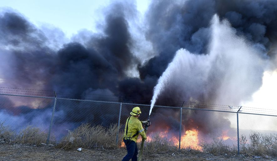 A firefighter battles a mulch and pallet fire burning out of control, fanned by Santa Ana winds in and around a recycling yard near Wilson Street and Fleetwood Drive in Riverside, Calif., Thursday, Dec. 3, 2020. Firefighters from both Riverside and San Bernardino County, along with assistance from Colton, Rialto and Riverside City Fire fought the blaze. (Will Lester/The Orange County Register via AP)