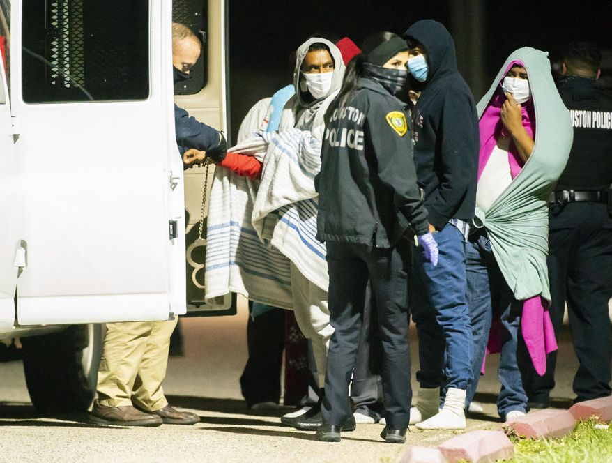 People are handcuffed together in pairs and loaded into vans as police investigate a possible human smuggling operation, Thursday night, Dec. 4, 2020, in Houston. About 30 people were taken to the gymnasium of a nearby elementary school and were eventually transported away. Investigators say the victims came from Mexico, Honduras, El Salvador and Cuba. (Mark Mulligan/Houston Chronicle via AP) ** FILE **