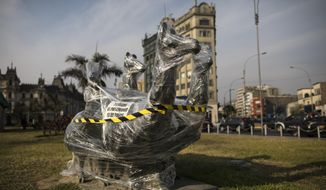 A bronze sculpture of four llamas is wrapped in plastic near the Palace of Justice in Lima, Peru, Saturday, Nov. 21, 2020. The municipality of Lima for the the first time in 485 years took precautions to protect historical monuments and statues, while Peru was mired in a whirlwind of demonstrations and a political crisis that resulted with three presidents in nine days. (AP Photo/Rodrigo Abd)
