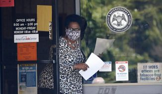 FILE - In this April 21, 2020 file photo, a worker wearing a mask to protect against coronavirus, holds an unemployment benefit application form as she waits for a client at the state WIN job center in Pearl, Miss.  Friday, Dec. 4,  monthly U.S. jobs report will help answer a key question hanging over the economy: Just how much damage is being caused by the resurgent coronavirus, the resulting restrictions on businesses and the reluctance of consumers to shop, travel and dine out?  (AP Photo/Rogelio V. Solis, File)