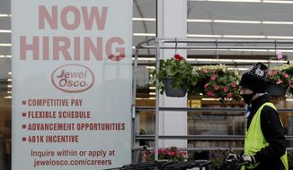 A man pushes carts as a hiring sign shows at a Jewel Osco grocery store in Deerfield, Ill., Thursday, April 23, 2020. On Friday, Dec. 4, monthly U.S. jobs report will help answer a key question hanging over the economy: Just how much damage is being caused by the resurgent coronavirus, the resulting restrictions on businesses and the reluctance of consumers to shop, travel and dine out? (AP Photo/Nam Y. Huh)