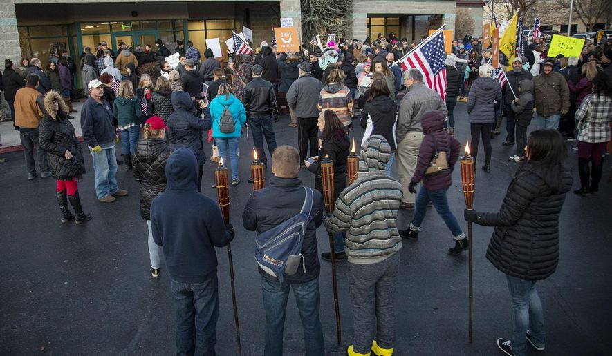 Anti-maskers, some carrying tiki torches, protest at the Central District Health offices during a special meeting of the board to decide on new mask mandates Friday, Dec. 4, 2020 in Boise, Idaho. (Darin Oswald/Idaho Statesman via AP)
