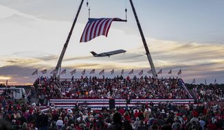 RETRANSMISSION TO CORRECT SPELLING OF PURDUE TO PERDUE - A jet takes off from Valdosta Regional Airport before the start of a rally featuring President Donald Trump for U.S. Senators Kelly Loeffler, R-Ga., and David Perdue, R-Ga., Saturday, Dec. 5, 2020 in Valdosta, Ga. President Trump's first political rally since losing the election is meant to boost Republican incumbents campaigning in the two Georgia runoffs that will decide which party controls the Senate. (AP Photo/Ben Gray)