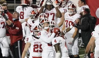 Indiana players celebrate in the final seconds of an NCAA college football game against Wisconsin Saturday, Dec. 5, 2020, in Madison, Wis.Indiana won 14-6. (AP Photo/Morry Gash)