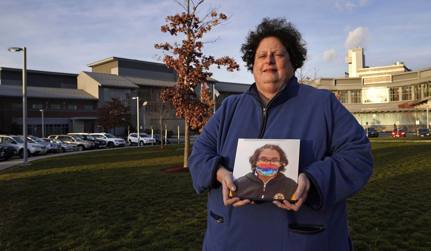 Laura Dilts, of Barre, Mass., holds a photograph of her 16-year-old son outside the Worcester Recovery Center, where he is a resident patient receiving assistance for his mental health, Monday, Nov. 23, 2020, in Worcester, Mass. The coronavirus pandemic has led to rising emergency room visits and longer waits for U.S. children and teens facing mental health issues. (AP Photo/Charles Krupa) **FILE**