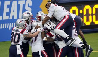 The New England Patriots celebrate after Devin McCourty returned a block field goal attempt for a touchdown during the first half of an NFL football game against the Los Angeles Chargers Sunday, Dec. 6, 2020, in Inglewood, Calif. (AP Photo/Ashley Landis)
