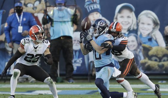 Tennessee Titans wide receiver Adam Humphries (10) loses control of the ball as he is hit by Cleveland Browns cornerback Terrance Mitchell (39) in the second half of an NFL football game Sunday, Dec. 6, 2020, in Nashville, Tenn. The Browns intercepted the ball on the play. (AP Photo/Ben Margot) **FILE**