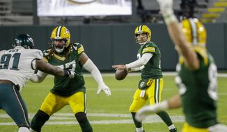 Green Bay Packers' Aaron Rodgers throws a pass during the first half of an NFL football game against the Philadelphia Eagles Sunday, Dec. 6, 2020, in Green Bay, Wis. (AP Photo/Mike Roemer)
