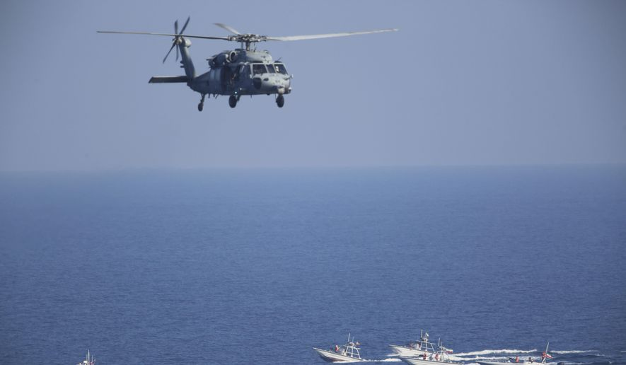 """FILE - In this Dec. 21, 2018 file photo, a U.S. MH-60 Seahawk helicopter flies over Iranian Revolutionary Guard patrol boats in the Strait of Hormuz. The top U.S. Navy official in the Mideast, said Sunday, Dec. 6, 2020, that America has reached an """"uneasy deterrence"""" with Iran after months of regional attacks and seizures at sea, even as tensions remain high between Washington and Tehran over the Islamic Republic's nuclear program. (AP Photo/Jon Gambrell, File)"""
