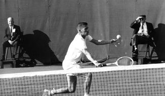 FILE - In this Sept. 3, 1965, file photo, Dennis Ralston, of Bakersfield, Calif., gets in position to return the ball during a first round singles match with Jim Hobson in the National Tennis Championships at Forest Hills in the Queens borough of New York. Ralston, a five-time Grand Slam doubles champion who was one of the initial players signed to the professional World Championship Tennis tour in the 1960s and an International Tennis Hall of Fame inductee, died Sunday, Dec. 6, 2020. He was 78. (AP Photo/File)