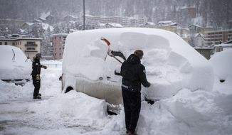 A member of Frensch ski team removes snow from a car with a shovel , in St. Moritz, Switzerland, Saturday, December 5, 2020. Due to a heavy snowfall and strong wind, the FIS decided to cancel today's women's Super-G race of the FIS Alpine Ski World Cup. (Jean-Christophe Bott/Keystone via AP)