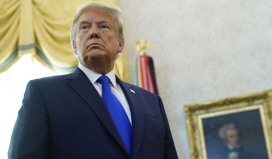 President Donald Trump listens to a reporter's question after awarding the Presidential Medal of Freedom, the highest civilian honor, to Olympic gold medalist and former University of Iowa wrestling coach Dan Gable in the Oval Office of the White House, Monday, Dec. 7, 2020, in Washington. (AP Photo/Patrick Semansky)