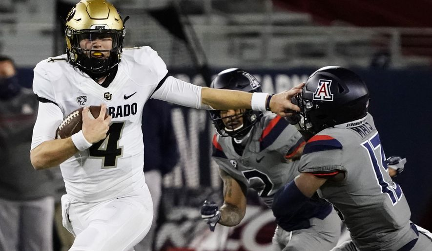 Colorado quarterback Sam Noyer (4) stiff-arms Arizona defensive back Isaiah Mays (13) in the second half during an NCAA college football game, Saturday, Dec. 5, 2020, in Tucson, Ariz. (AP Photo/Rick Scuteri)