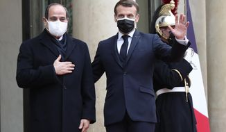 French President Emmanuel Macron, right, and Egyptian President Abdel-Fattah el-Siss gesture upon el-Sissi arrival at the Elysee palace, Monday, Dec. 7, 2020 in Paris. Egyptian President Abdel-Fattah el-Sissi is paying a state visit to France for talks on fighting terrorism, the conflict in Libya and other regional issues, amid criticism from human rights groups over the Egyptian leader's crackdown on dissent. (AP Photo/Michel Euler)