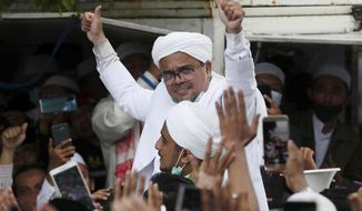 FILE - In this Tuesday, Nov. 10, 2020, file photo, Indonesian Islamic cleric and the leader of Islamic Defenders Front Rizieq Shihab, center, gestures to his followers as he arrives from Saudi Arabia in Jakarta, Indonesia. Tuesday, Nov. 10, 2020. Officers early Monday fatally shot six suspected followers of the Islamic Defenders Front, police said. (AP Photo/Achmad Ibrahim, File)