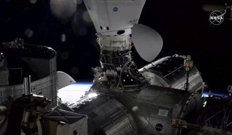 In this image taken from NASA TV the Dragon cargo capsule docks at the International Space Station, Monday, Dec. 7, 2020, alongside a Dragon crew capsule that carried up astronauts three weeks ago. (NASA via AP)