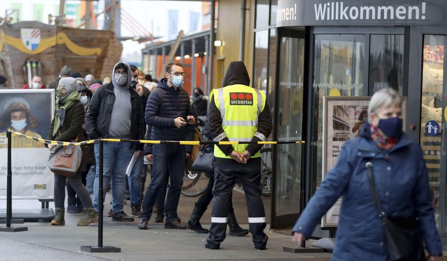 People line up in front of a shop after the stores reopen after a lock down in Vienna, Austria, Monday Dec. 7, 2020., 2020. The Austrian government has moved to restrict freedom of movement for people, in an effort to slow the onset of the COVID-19 coronavirus. (AP Photo/Ronald Zak)